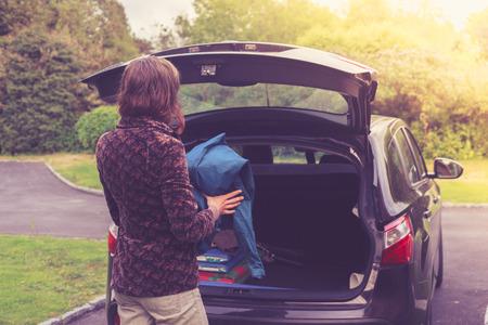 tronco: Una joven mujer se está abriendo el maletero de un coche Foto de archivo