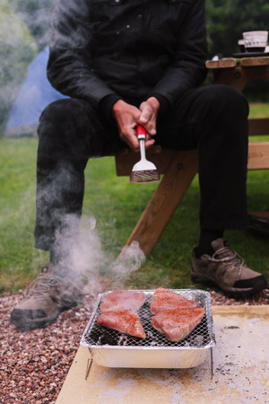 A senior man is looking after a barbecue outside in a garden photo