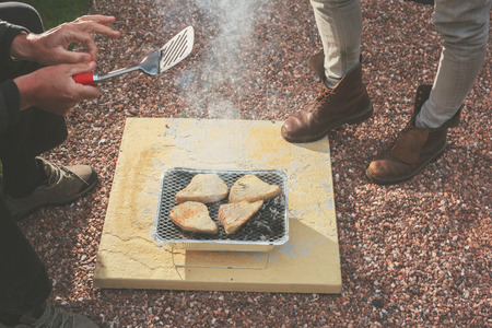 Two people are standing around a disposable barbecue outside photo