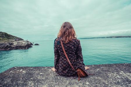 Une jeune femme est assise au bord de l'eau dans un port
