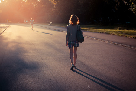 walking away: A young woman is walking into the sunset in a park