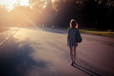 A young woman is walking into the sunset in a park photo