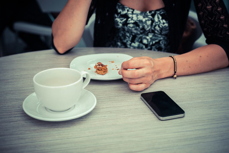 A Young woman is having coffee and is watching her phone photo