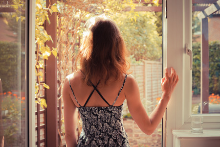 A young woman is standing in the doorway of her kitchen and is looking at the garden at sunrise photo