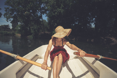 water filter: A young woman is rowing a boat on a summer day