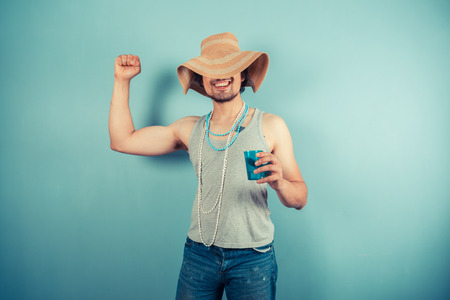 A happy young man wearing a beach hat and pearl necklaces is drinking from a blue cup photo
