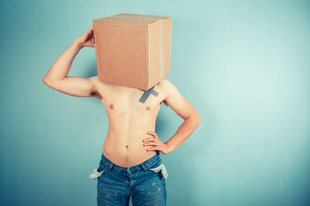carboard box: A confused young man is wearing a cardboard box on his head