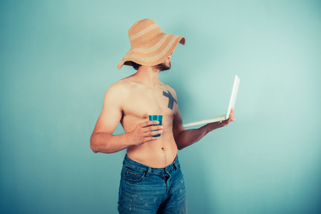 A young shirtless man wearing a large beach hat is holding a cup and a laptop photo