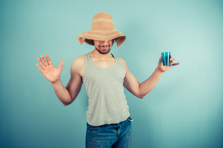 A happy young man wearing a beach hat is drinking from a blue cup photo