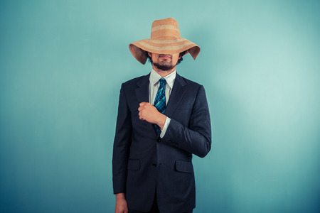 A young businessman is wearing a large beach hat Stock Photo - 29625545