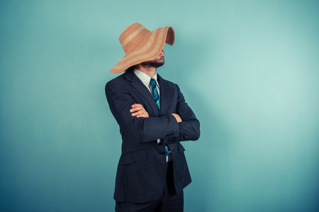 A young businessman is wearing a large beach hat Stock Photo - 29625547