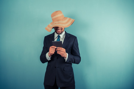 A young businessman wearing a large beach hat is reading on a tablet Stock Photo - 29625549