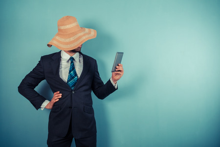 A young businessman wearing a large beach hat is reading on a tablet Stock Photo - 29625550