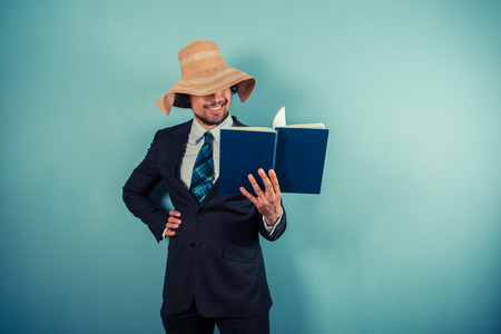 A businessman wearing a beach hat is reading a book Stock Photo - 29625552