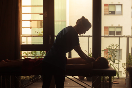 The silhouette of a masseuse as she is treating a client on a massage table