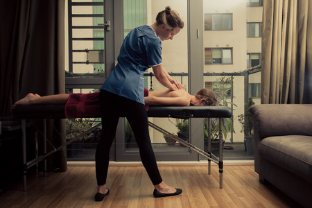 osteopathy: A massage therapist is treating a female client on a table in an apartment