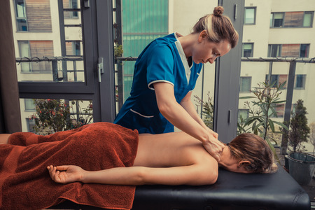 A massage therapist is treating a female client on a table in an apartment