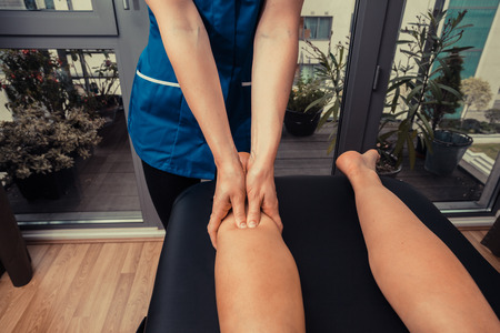 A woman is getting her legs massaged by a therapist Stock Photo