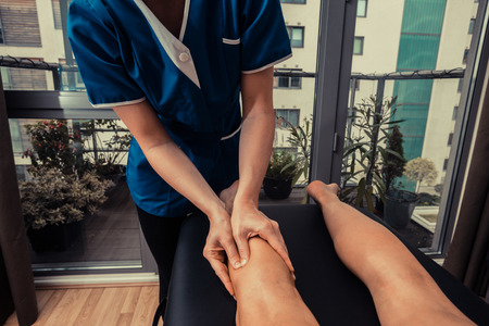 A woman is getting her legs massaged by a therapist photo