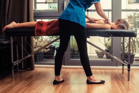 A massage therapist is treating a female client on a table by the window photo