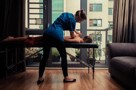 마사지 치료사는 아파트에서 테이블에 여성 클라이언트를 치료한다