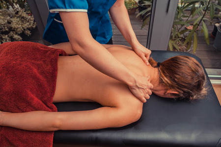 A massage therapist is treating a female client on a table in an apartment photo