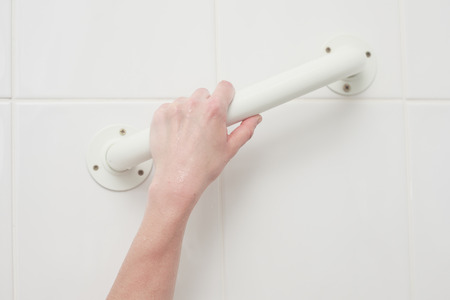 handle: A female hand is grabbing an assistive handle in the bathroom Stock Photo