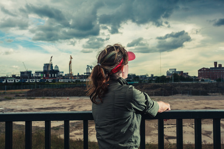 A young woman is looking at a vast  construction site with city in the distance photo