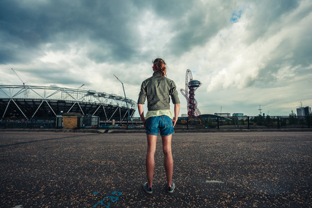 LONDON - JULY 7  Young woman standing outside The Orbit and Stadium at the Queen Elizabeth Olympic Park on July 7, 2014 in Stratford, London, UK