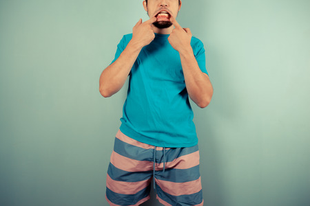 A young man in striped shorts is pulling silly faces Stock Photo