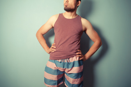 A young man in striped shorts is standing with his hands on his hips Stock Photo - 29973433