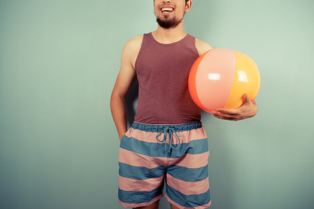 A happy young man wearing a vest is holding beach ball Stock Photo - 29973434