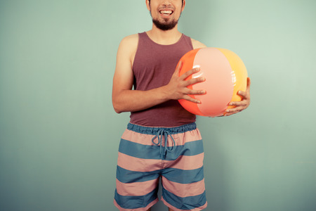A happy young man wearing a vest is holding beach ball Stock Photo - 29973435
