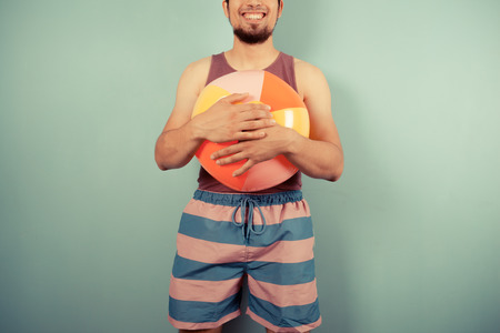 A happy young man wearing a vest is holding beach ball Stock Photo - 29973436
