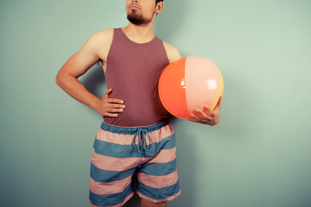 A young man in a vest and striped shorts is holding beach ball Stock Photo - 29973438