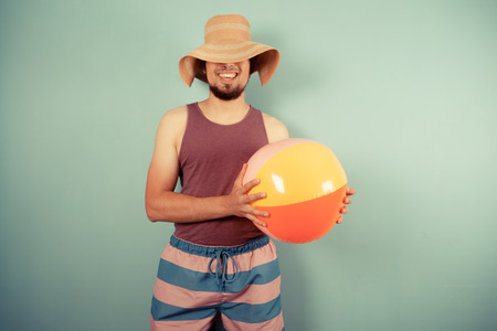 A happy young man wearing a sun hat is holding beach ball Stock Photo - 29973440