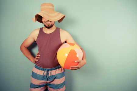 A happy young man wearing a sun hat is holding beach ball Stock Photo - 29973441