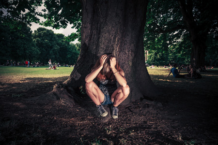A tired an depressed young woman is sitting under a big tree in the park photo