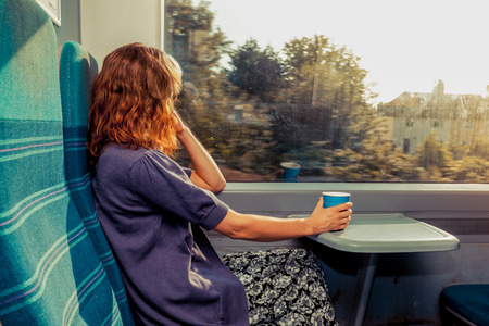 若い女性はコーヒーのカップで電車の中で座っていると外を見ています。 写真素材
