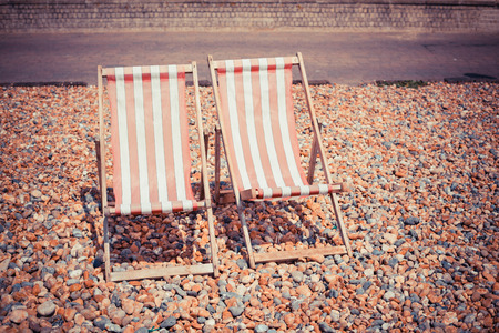 Two deck chairs on a pebble beach photo