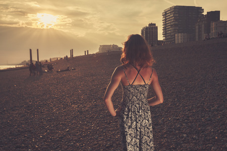 A young woamn wearing a dress is standing on the beach and looking at the sunset photo