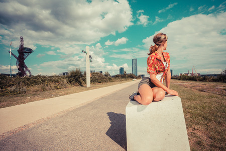 A young woman is sitting outside and is looking at a cityscape photo