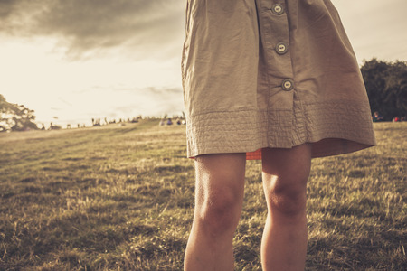 A young womans skirt is blowing in the wind as she is standing in a park at sunset photo
