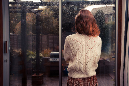 A young woman is standing by the french doors in her house and is looking out at the rain