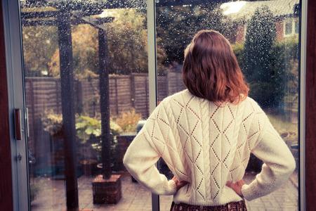 dentro fuera: Una mujer joven est� de pie junto a las puertas francesas en su casa y est� mirando hacia fuera en la lluvia