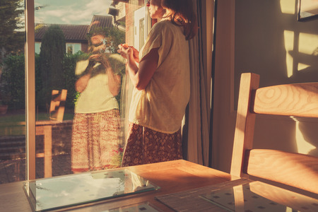 french doors: A young woman is standing by the french doors of her home at sunset