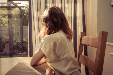 hopeful: A young woman is sitting at a table at sunset and is looking out the window Stock Photo