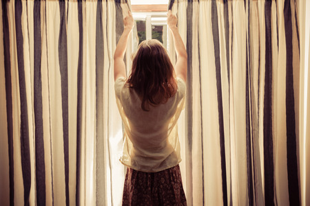 window curtains: A young woman is opening the curtains at sunrise