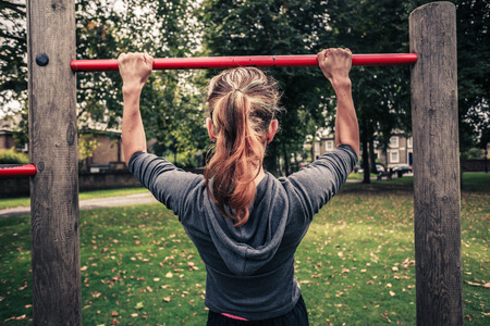 pullups: A young woman is doing pullups in the park