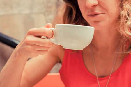 A young woman is drinking coffee photo